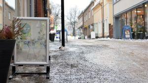 Skyltar på en gågata som är isbeklädd och har sandats. Himlen är grå.