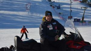 Jari Lehtinen, en man med svart jacka och svart mössa, sitter på en snöskoter. Bakom honom kommer en utförsåkare i röd jacka ner för skidbacken.