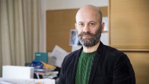 Mikko Tamminen iklädd en grön tröja och mörk kavaj. Han står i ett kontor, tittar in i kameran och ler.
