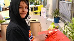 En pojke skär chili.