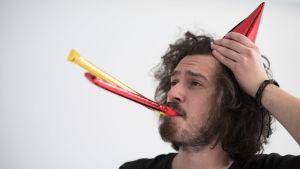 En man med röd partyhatt blåser i färggranna visselpipor.