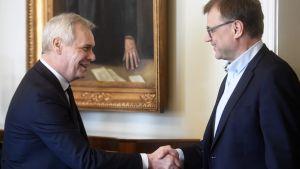 Antti Rinne och Juha Sipilä skakar hand.