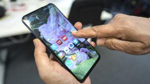 En hand håller i en Huawei Honor View 20 smarttelefon och tittar på nyhetsappar.