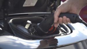 en hand kopplar en laddningskontakt för en elbil under motorhuven