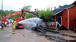 Räddningspersonal som står och sprutar vatten på en röd boda med svart tak.