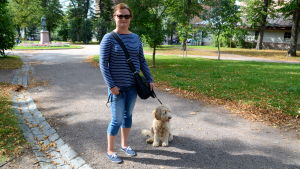En kvinna med en hund i koppel står i en park.