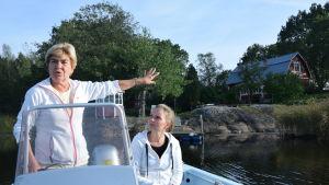 Två kvinnor i en båt. Den ena står och pekar mot ett hus medan den andra sitter och tittar på.