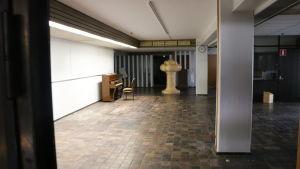 Tom hall med brunt golv och vit pelare. Mot väggen står ett piano och en stol.