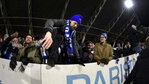 En man iklädd blå mössa och fotbollshalsduk är på väg att klättra över kanten som skiljer läktaren från fotbollsplanen.