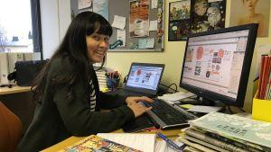En ung kvinna sitter vid ett skrivbord och arbetar med en dator.