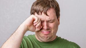 En man torkar tårar med handen från sina ögon.