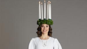 Finlands lucia 2019 Sara Ray med krona med tända ljus och vit särk med rött band.