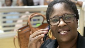 Jessie håller en mobiltelefon mot örat. Hon har jobbat på Lifeline/Childline Zambia i fem år.