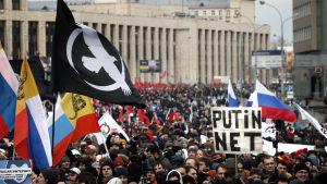 """Människor demonstrerar i Moskva med flaggor och skyltar, på en står det """"Putin njet"""""""