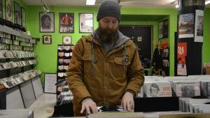 En man med skägg bläddrar bland skivorna.