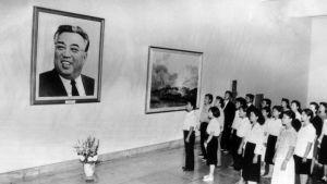 Mustavalkeassa kuvassa joukko pohjoiskorealaisia seisoo huoneessa, jonka seinällä on valtava Kim Il Sungin kuva.