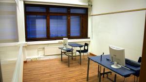 Rum med bord, stolar och datorskärmar