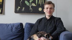 Komikern Alfred Backa  sitter i en soffa med sin katt i famnen.