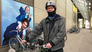 En man som håller i sin cykel.