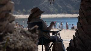 Dam som sitter i skuggan på en strand på Teneriffa