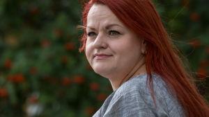 Närbild på rödhåriga kvinna mot en huvudsakligen grön bakgrund. På bilden Tehys ordförande Millariikka Rytkönen i Borgå.