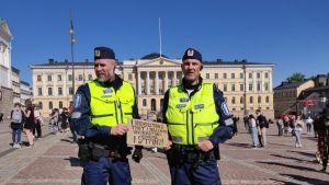 Två poliser står med ett plakat med antirasistiskt budskap.