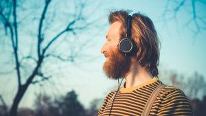 Man med hörlurar på huvudet lyssnar.