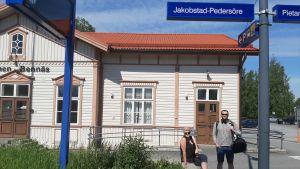 Två personer framför Jakobstad-Pedersöre tågstation.