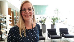 En kvinna i prickig blus står i ett kontorslandskap