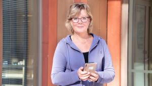 Kvinna står med telefon i handen vid rödorange utevägg.
