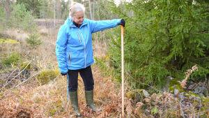 En kvinna som har handen på en käpp som satts ner i skogen.