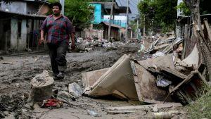 En man går på en orkanförstörd, gyttjig gata.