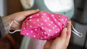 En person håller upp ett rosa munskydd av tyg.