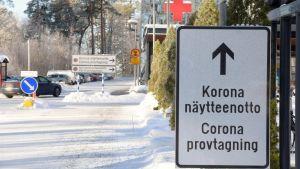 Skylt som säger coronaprovtagning. I bakgrunden syns bilparkering. Snö på marken.