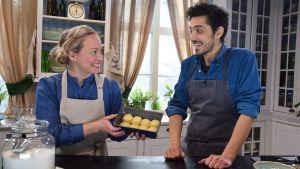 En kvinna och en man i ett kök ler mot varandra vid ett bord