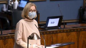 Riksdagsledamot Anneli Kiljunen står i en talarstor. Hon har munskydd.