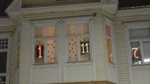 Ett hus med flera upplysta nummer i fönstren som en fönsterjulkalender.