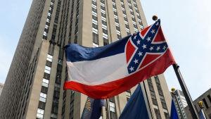 En bild på Mississippis flagga. Uppifrån och ner har den tre ränder i blått vitt och rött. Till höger på flaggan är det ett fyrkantigt rött fält med ett blått kryss över med vita stjärnor - den såkallade sydstatssymbolen.