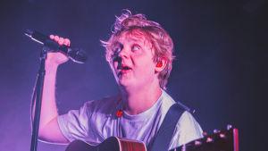 Laulaja Lewis Capaldi seisoo Tavastian lavalla kitara kaulassaan velmu ilme naamallaan.