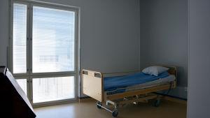 En säng för en äldre person står nära ett fönster i ett rum.