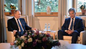 Rysslands president Vladimir Putin sitter inomhus på gullranda tillsammans med Finlands presdient Sauli Niinistö.