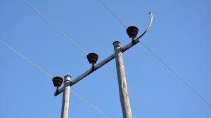 ellinjer och -stolpe mot blå himmel