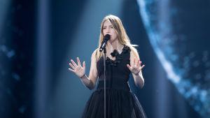 Kvinna i svart klänning sjunger i mikrofon