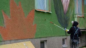 Rustam Qbic målar konturerna med en pensel.
