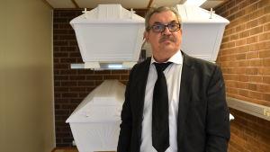 Begravningsentrepenör Lars Andersson med vita kistor.
