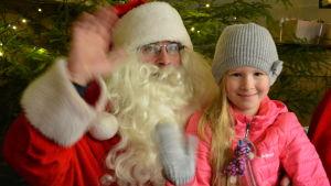 Flicka sitter i julgubbens famn.
