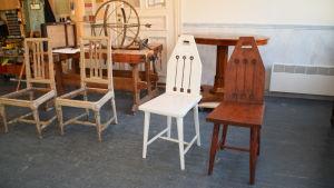 En bild på två stolar, en vit och en träfärgad. Den vita ska restaureras så att den ser ut som den träfärgade. I bakgrunden syns andra möbler som ska restaureras i ateljen,