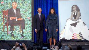 Barack och Michelle Obama poserar bredvid sina porträtt