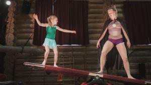 Sirkuksen keinulaudalla pieni tyttö ja aikuinen nainen sirkusasuissa.