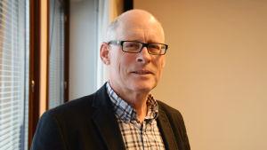 En bild på en man i skjorta och kavaj som står i sitt kontor. Han har glasögon. Mannen heter Henrik Ekblom.